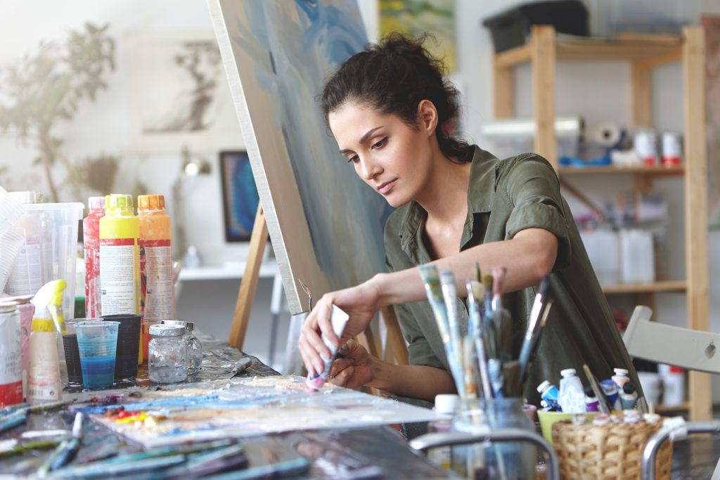 Picture of serious concentrated young Caucasian female artist sitting at desk with painting accessories, holding tube of oil paint, mixing colors on palette; unfinished painting on canvas near her